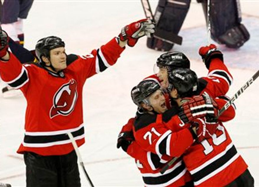 The puck is seen in the goal as New Jersey Devils' Jacob Josefson, right, of Sweden, is congratulated by teammates Mattias Tedenby (21), of Sweden, Anton Volchenkov, back, of Russia, and David Clarkson, left, after Josefson's goal during the third period of an NHL hockey game against the Atlanta Thrashers, Tuesday, March 15, 2011, in Newark, N.J. The Devils won 4-2. (AP Photo/Julio Cortez)