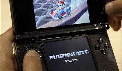 FILE - In this Sept. 29, 2010 file photo, a visitor operates a Nintendo 3DS featuring 3-D imagery during a press conference by Nintendo Co. Nintendo Corp. has warned that the 3-D screen on its new 3DS handheld game device shouldn't be used by children 6 or younger because it may harm their immature vision.(AP Photo/Shuji Kajiyama, file)