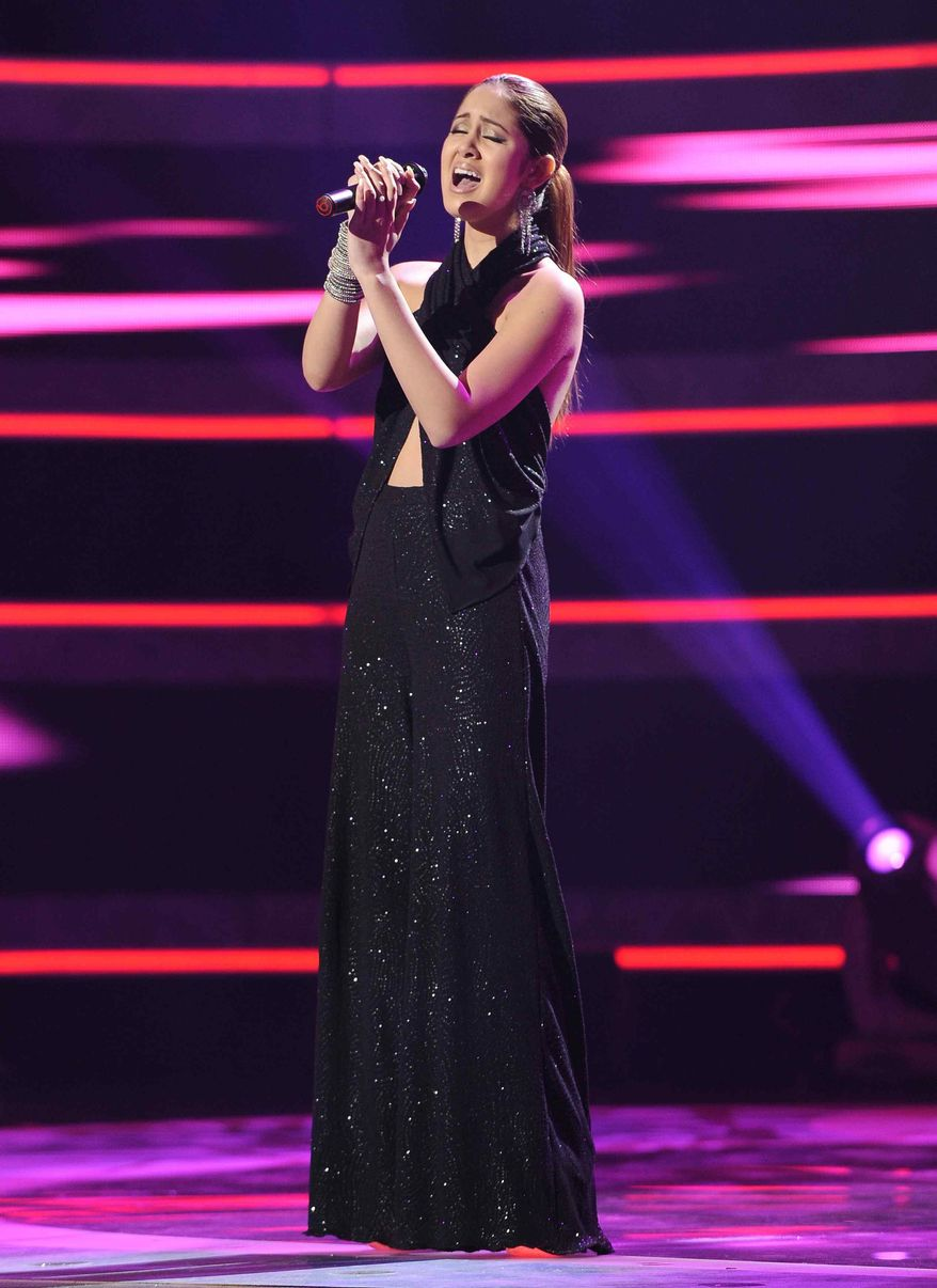 """In this publicity image released by Fox, Karen Rodriguez performs on the singing competition series """"American Idol,"""" on Wednesday, March 9, 2011, in Los Angeles. (AP Photo/Fox, Ray Mickshaw)"""