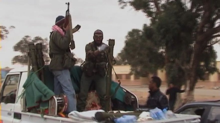 This image taken from video shows rebels on the back of a vehicle in the area of Benina, a civilian and military airport, outside Benghazi in eastern Libya on Thursday, March 17, 2011. Libyan rebels shot down at least two bomber planes that attacked the airport in their main stronghold of Benghazi Thursday, according to residents who witnessed the rare success in the struggle against Moammar Gadhafi's superior air power. (AP Photo/APTN)