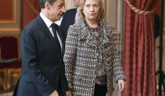 U.S Secretary of state Hillary Clinton, right, and French President Nicolas Sarkozy walk in the Elysee Palace in Paris, during a crisis summit on Libya Saturday, March, 19, 2011. Britain and France took the lead in plans to enforce a no-fly zone over Libya on Friday, sending British warplanes to the Mediterranean and announcing a crisis summit in Paris with the U.N. and Arab allies.(AP Photo/Lionel Bonaventure, Pool)