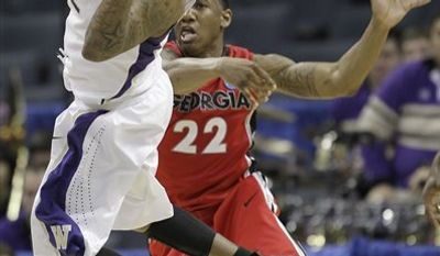 Washington guard Isaiah Thomas (2) passes the ball as Georgia guard Gerald Robinson (22) defends in the second half of a East Regional NCAA tournament second round college basketball game, Saturday, March 19, 2011, in Charlotte, N.C. (AP Photo/)