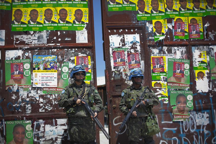 U.N. peacekeepers from Brazil stand guard at the gate of a polling station ahead of Sunday's second round of presidential elections in the Cite Soleil section of Port-au-Prince, Haiti, on Saturday, March 19, 2011. (AP Photo/Ramon Espinosa)