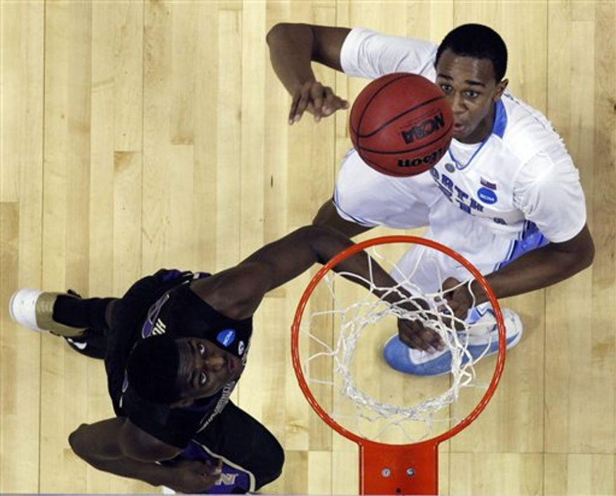North Carolina forward John Henson, right, and Washington forward Justin Holiday wait for a loose ball in the second half of an East Regional NCAA tournament third-round college basketball game, Sunday, March 20, 2011, in Charlotte, N.C. (AP Photo/Chuck Burton)