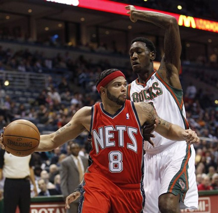 New Jersey Nets' Deron Williams (8) drives past Milwaukee Bucks' Larry Sanders during the first half of an NBA basketball game Friday, March 18, 2011, in Milwaukee. (AP Photo/Morry Gash)