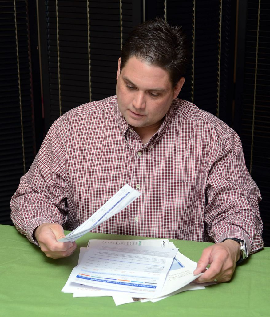 Brett Hacker looks over his 401(k) statements, which show that his retirement account is growing once again after the balance sank when the stock market did. (Associated Press)