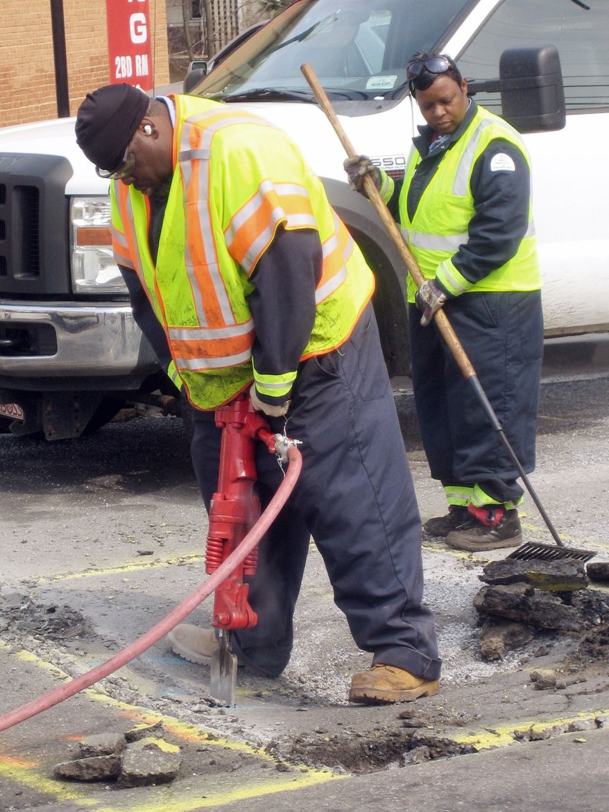 A D.C. road crew repairs potholes in the 1300 block of Jasper Place Southeast on Monday. (Meredith Somers/The Washington Times)