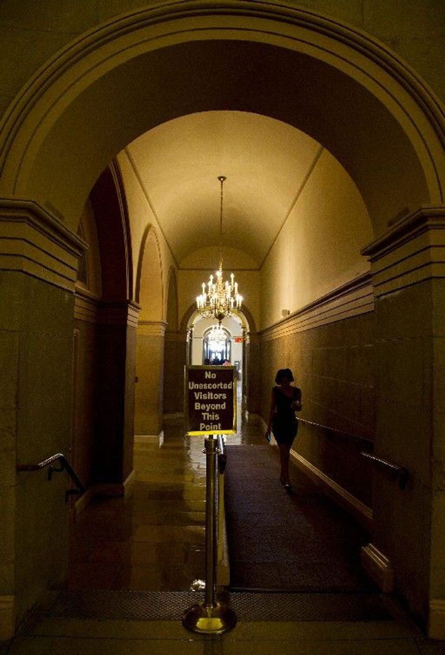 A woman walks through a deserted hallway of the U.S. Capitol on Monday. Despite the fact that the United States began attacking Libya a few days ago, lawmakers have been away for 10 days. (Barbara L. Salisbury/The Washington Times)
