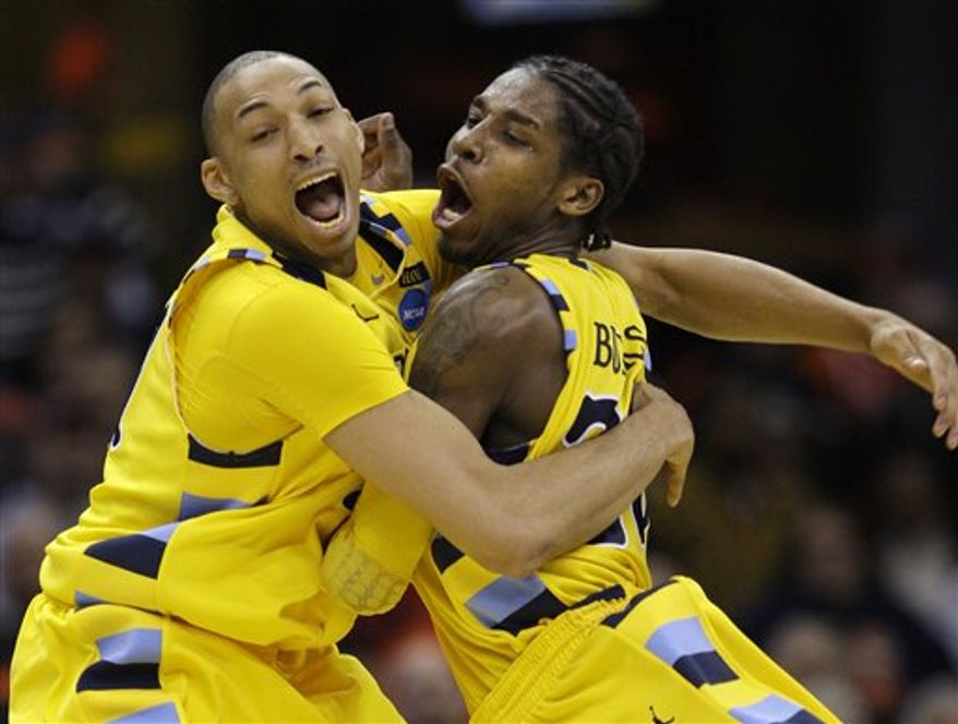 Marquette's Joseph Fulce, left, and Dwight Buycks celebrate a 66-62 win over Syracuse in an East regional NCAA college basketball tournament third-round game, Sunday, March 20, 2011, in Cleveland. Marquette advances to the Sweet 16. (AP Photo/Tony Dejak)