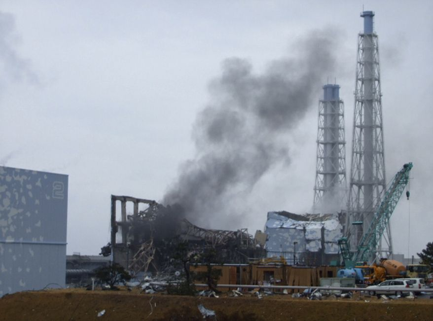In this photo released by Tokyo Electric Power Co. (TEPCO), gray smoke rises from Unit 3 of the tsunami-stricken Fukushima Dai-ichi nuclear power plant in Okumamachi, Fukushima Prefecture, Japan, on Monday, March 21, 2011. Officials said that TEPCO temporarily evacuated its workers from the site. At left is Unit 2 and at right is Unit 4. (AP Photo/Tokyo Electric Power Co.)