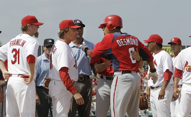 Washington Nationals' Ian Desmond (6) is held back from St. Louis Cardinals manager Tony La Russa during the seventh inning of a spring training baseball game, Monday, March 21, 2011 in Jupiter, Fla. Desmond was hit on a pitch by Cardinals pitcher Miguel Batista. (AP Photo/Carlos Osorio)