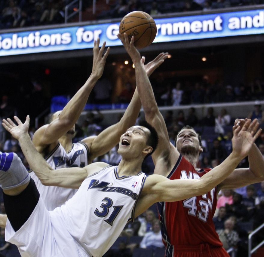 Washington Wizards power forward Yi Jianlian (31), of China, falls backward while vying for a rebound against New Jersey Nets power forward Kris Humphries (43) during the fourth quarter of an NBA basketball game at the Verizon Center in Washington, on Sunday, March 20, 2011. The Wizards won 98-92. (AP Photo/Jacquelyn Martin)