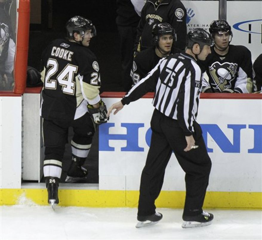 In this photo from March 20, 2011, Pittsburgh Penguins' Matt Cooke (24) is escorted from the ice by NHL linesman Derek Amell (75) after he was elected for elbowing New York Rangers defenseman Ryan McDonagh in the third period of the NHL hockey game in Pittsburgh. The league announced on Monday March 23, 2011 that Cooke has been suspended for the remainder of the regular season (10 games) and the first round of the Stanley Cup Playoffs for the infraction.  (AP Photo/Keith Srakocic)