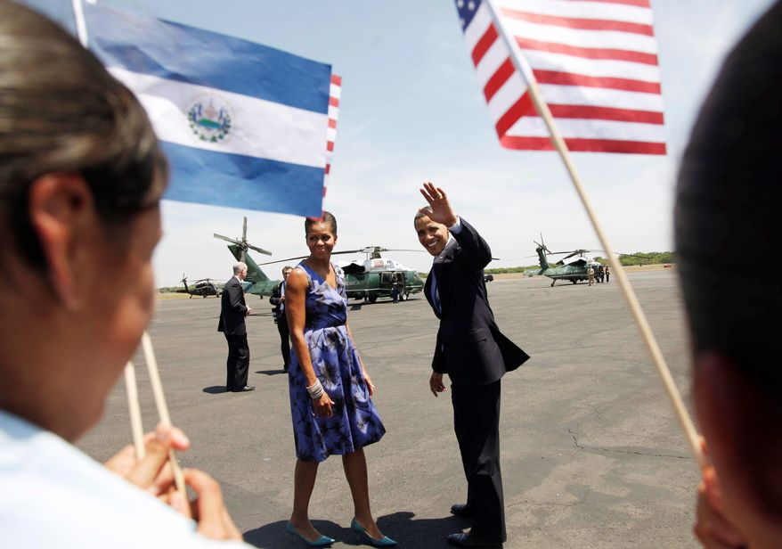 President Obama, with first lady Michelle Obama, waves from the tarmac after arriving in San Salvador, El Salvador, on Tuesday. He and Salvadoran President Mauricio Funes announced several partnerships. (Associated Press)