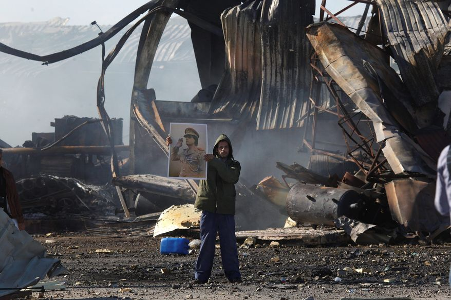 A supporter of Col. Moammar Gadhafi displays the Libyan leader's portrait Tuesday amid the wreckage of a Tripoli naval base warehouse hit by missiles Monday. (Associated Press)