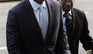Barry Bonds, center, arrives with an unidentified man, right, for his criminal trial at a federal courthouse in San Francisco on Thursday, March 24, 2011. (AP Photo/Paul Sakuma)
