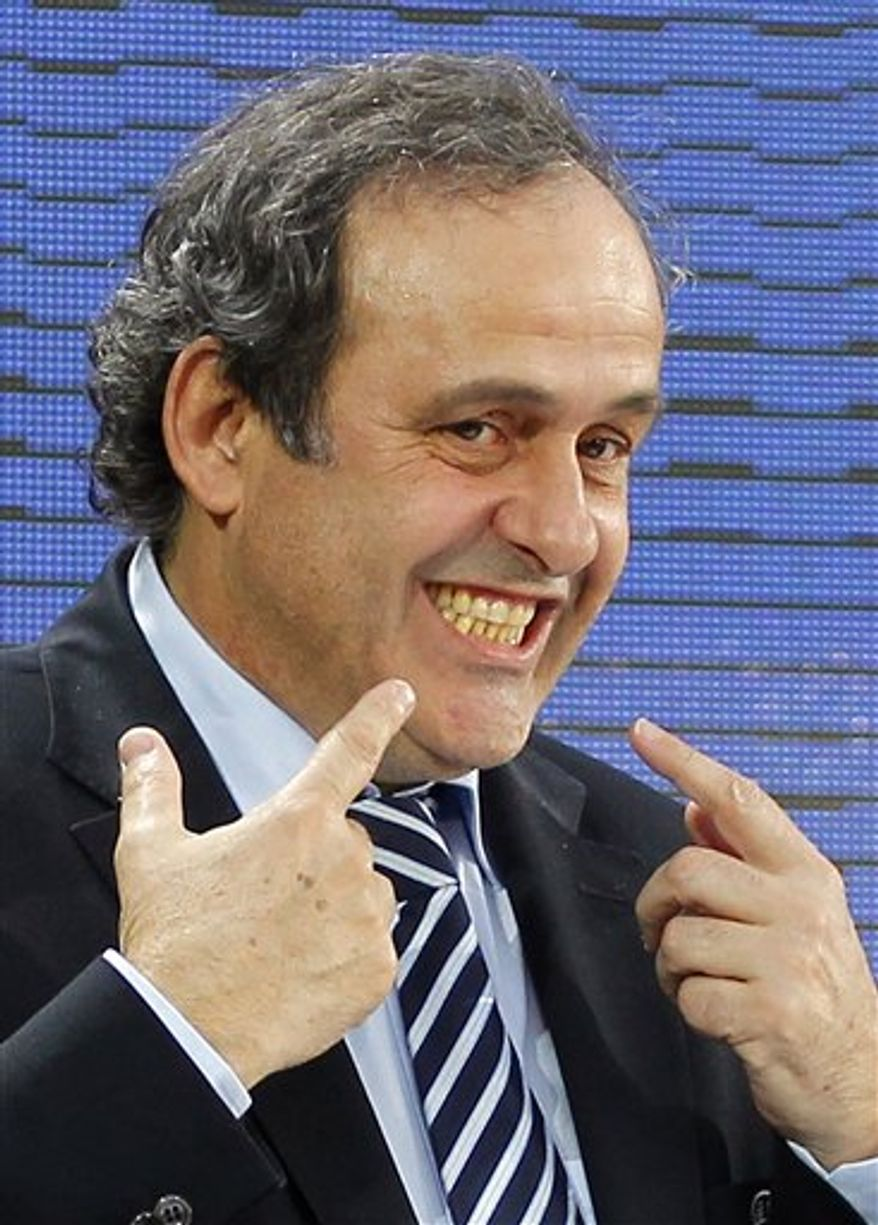 UEFA president Michel Platini of France smiles to acknowledge applause after being re-elected during the 35th Ordinary UEFA Congress at the Grand Palais in Paris, France, Tuesday, March 22, 2011. Platini has been re-elected as UEFA President until 2015 by acclaim of Europe's 53 football nations. (AP Photo/Francois Mori)