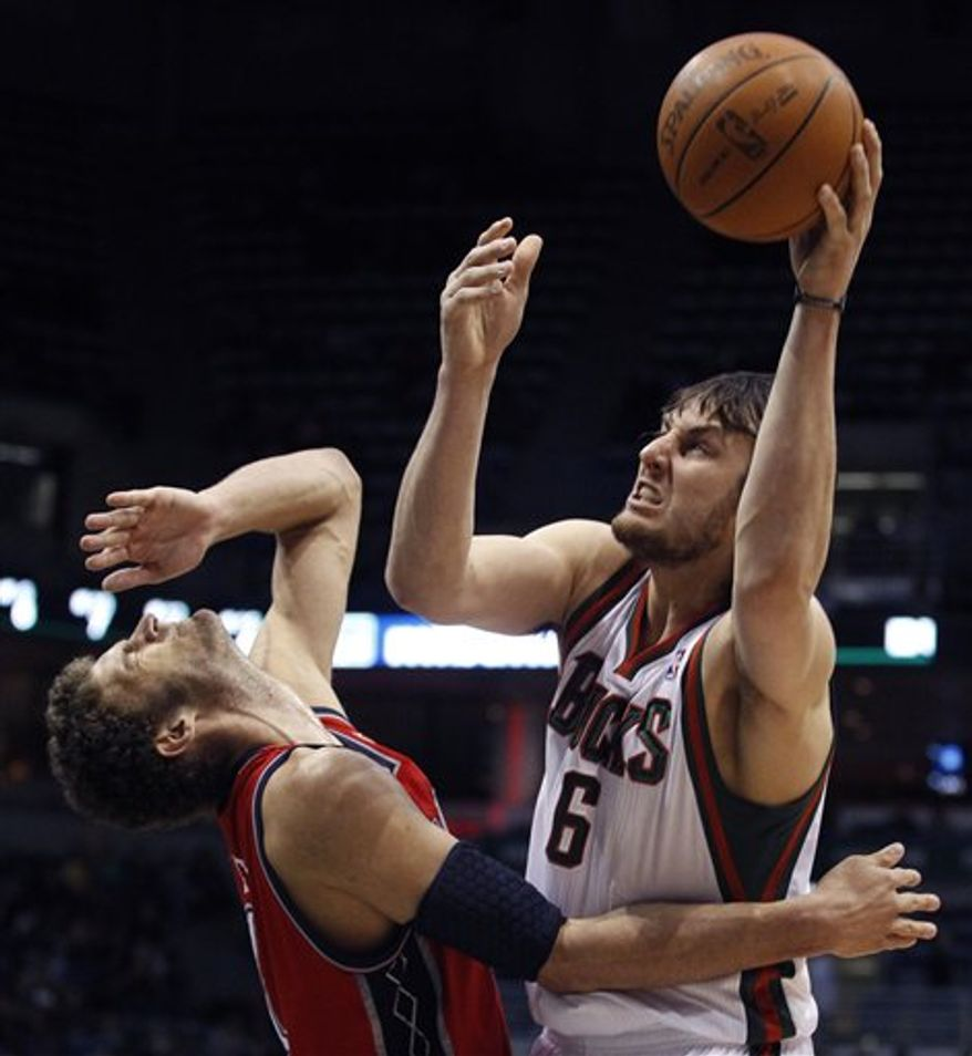 Milwaukee Bucks' Andrew Bogut (6) fouls New Jersey Nets' Brook Lopez as Bogut goes up for a shot during the second half of an NBA basketball game Friday, March 18, 2011, in Milwaukee. The Bucks won 110-95. (AP Photo/Morry Gash)