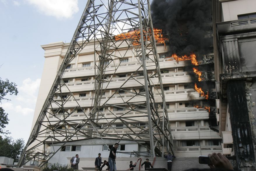Flames engulf part of the Interior Ministry complex in Cairo on Tuesday, March 22, 2011. An Egyptian security official said police protesting in front of ministry set fire to a part of the downtown complex that houses the agency's personnel department. (AP Photo/Mohammed Abu Zaid)