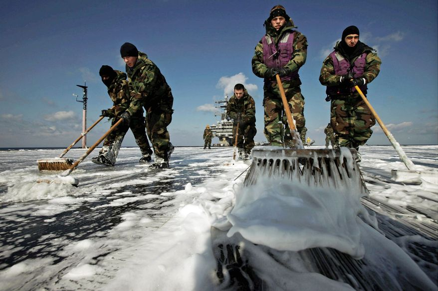The crew of the USS Ronald Reagan swabs the aircraft carrier's deck to remove radiation fallout after 10 days of delivering supplies to survivors of the earthquake and tsunami. (Associated Press)