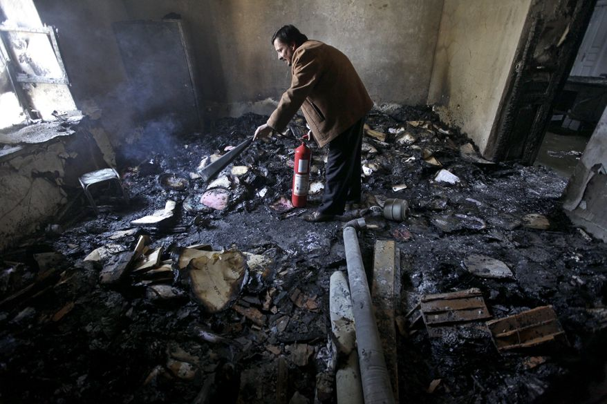 """A Syrian man damps down with a fire extinguisher a burned court room that was set on fire by Syrian anti-government protesters, in the southern city of Daraa, Syria, on Monday, March 21, 2011. Mourners chanting """"No more fear!"""" have marched through a Syrian city where anti-government protesters had deadly confrontations with security forces in recent days. (AP Photo/Hussein Malla)"""