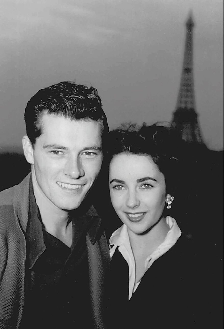In this May 31, 1950 file photo, actress Elizabeth Taylor poses with her new husband, hotel heir Nick Hilton, as they stand on the terrace of their hotel room in Paris while on their honeymoon. Publicist Sally Morrison says Taylor died Wednesday, March 23, 2011 in Los Angeles of congestive heart failure at age 79. (AP Photo/File)
