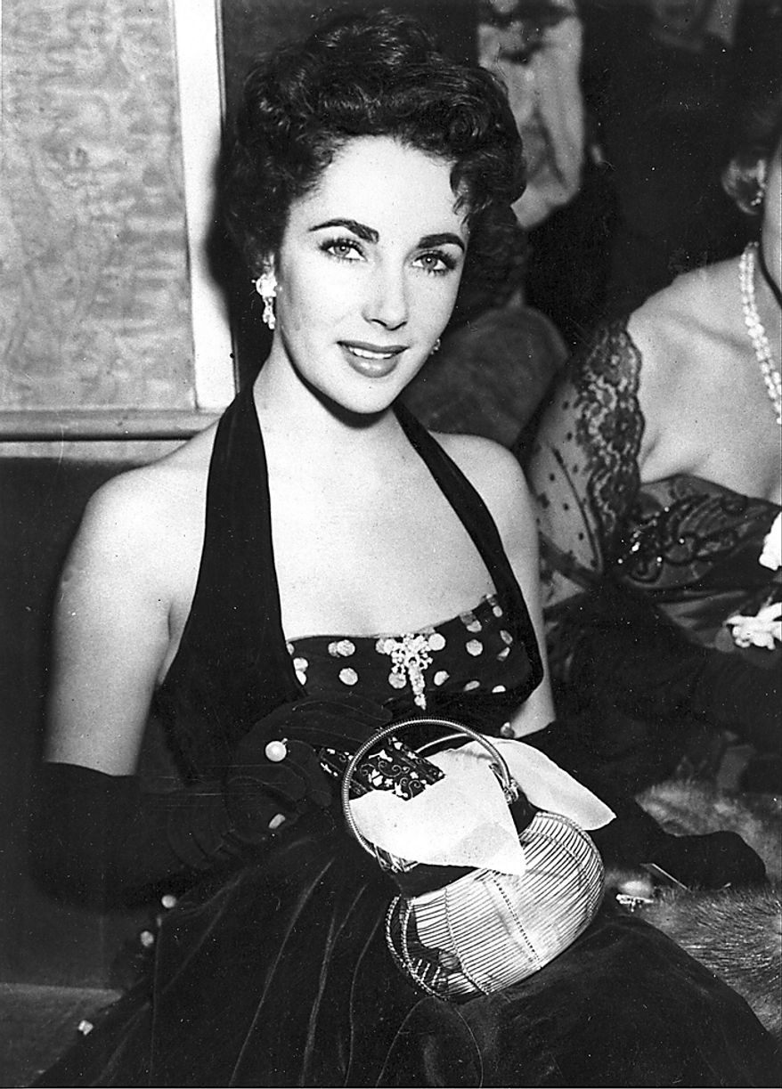 """In a Sept. 22, 1951 file photo, Elizabeth Taylor is shown at the premiere of """"The Lady with the Lamp"""" at the Warner Theater in London. Publicist Sally Morrison says the actress died Wednesday, March 23, 2011 in Los Angeles of congestive heart failure at age 79. (AP Photo/File)"""