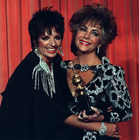In this Jan. 27, 1985 file photo, Liza Minelli, left, hugs actress Elizabeth Taylor, who holds her Cecil B. DeMille award in Beverly Hills, Calif.  Publicist Sally Morrison says Taylor died Wednesday, March 23, 2011 in Los Angeles of congestive heart failure at age 79. (AP Photo/Lennox McLendon, File)