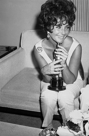 """In this April 19, 1961 file photo, actress Elizabeth Taylor holds the Oscar she won as 1960's best film actress for her role in """"Butterfield 8,"""" while speaking with reporters in Hollywood, Calif.  Publicist Sally Morrison says the actress died Wednesday, March 23, 2011 in Los Angeles of congestive heart failure at age 79. (AP Photo/File)"""