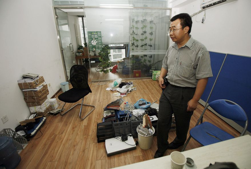 """Chinese lawyer Jiang Tianyong scans the half-empty office of the Gongmeng rights group's legal research center after it was closed in July 2009 by Chinese authorities. The last time he was seen, police were throwing him into a van in February while visiting his brother's house near Beijing. """"None of them will tell me anything about why he was taken away or where he has been taken to,"""" his wife, Jin Bianling, said. """"I worry about him all the time. What if the police are torturing him?"""" (Associated Press)"""