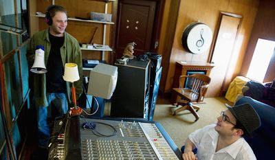 David Somerville (left), who sings backup and plays sax, flute, trumpet and keyboard for the Samsarians, looks to RVA Studios owner Aaron Reinhard for a cue to start singing during a recording session. (Barbara L. Salisbury/The Washington Times)