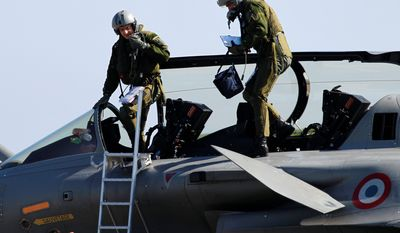 French air force pilots exit from a Rafale jet fighter at Solenzara 126 Air Base on Corsica island in the Mediterranean Sea on Thursday after coming back from a mission to Libya. NATO announced an agreement to take over the command of the U.S.-led air war over Libya, which saved the ragtag resistance that was nearly defeated last week.