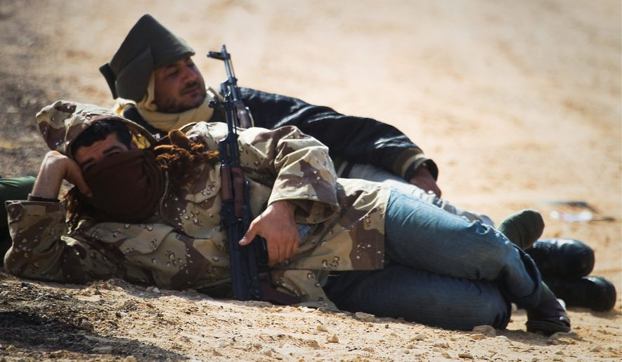 Libyan rebels take a rest at a checkpoint at the front line near Zwitina on the outskirts of Ajdabiya in eastern Libya on Thursday. (Associated Press)