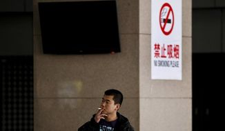 A Chinese man sits on a bench while holding a cigarette in his fingers in front of a pillar with a no smoking notice on display at a bus station in Beijing Thursday, March 24, 2011. On this week, Chinese health authorities renewed a push to ban smoking in indoor public places, adding more venues like hotels and restaurants as of May 1, though still excluding many workplaces. (AP Photo/Andy Wong)