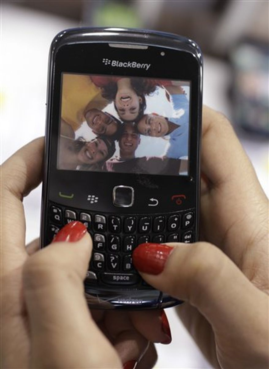 In this March 22, 2011 photo, a customer looks at a Research In Motion Blackberry Torch using a AT&T carrier, at a Best Buy in Mountain View, Calif. Research In Motion Ltd. releases quarterly financial results Thursday, March 24, after the market close. (AP Photo/Paul Sakuma)