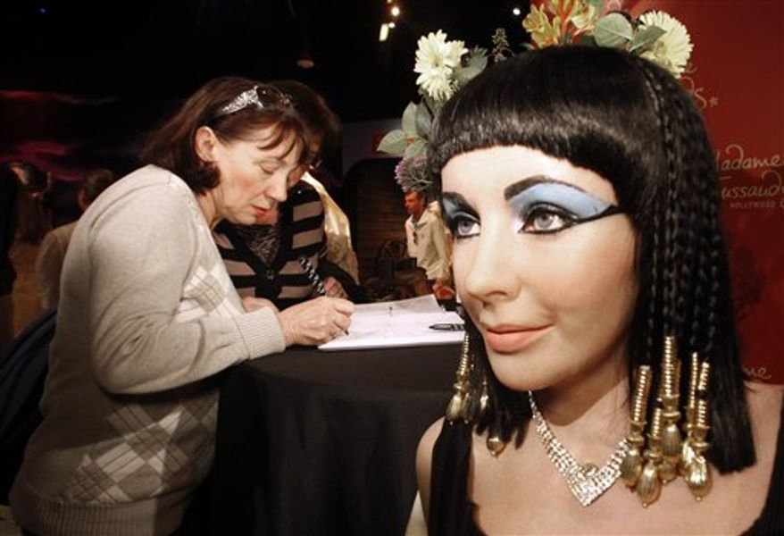 """Visitors sign a condolence book next to a figure of actress Elizabeth Taylor in her title role in the 1963 film, """"Cleopatra,"""" at Madame Tussauds Hollywood wax museum in Los Angeles Wednesday, March 23, 2011.  Taylor died early Wednesday of congestive heart failure at the age of 79.  (AP Photo/Reed Saxon)"""