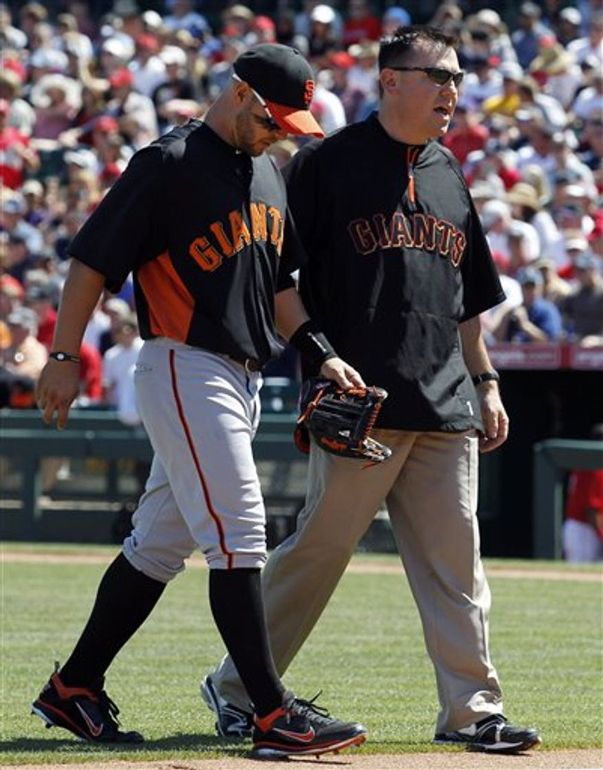 San Francisco Giants right fielder Cody Ross limps off the field with aid of a trainer during the first inning of a spring training baseball game against the Los Angeles Angels in Tempe, Ariz., Wednesday, March 23, 2011. (AP Photo/Chris Carlson)