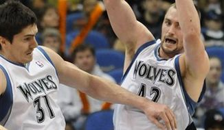 Minnesota Timberwolves' Darko Milicic, of Serbia, left, gets out of the way as teammate Kevin Love grabs the rebound during the first half of an NBA basketball game against the Sacramento Kings, Sunday, March 20, 2011 in Minneapolis. (AP Photo/Jim Mone)