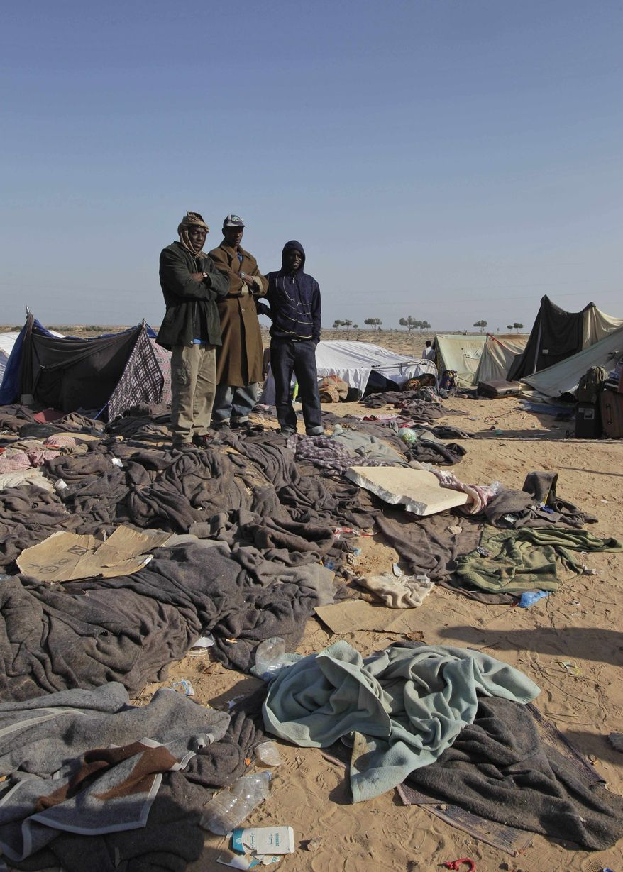 Men who used to work in Libya and fled the unrest in the country, wait for buses in order to be repatriated, in a refugee camp at Ras Ajdir, near Tunisia-Libya border, Tunisia, Friday, March 25, 2011. (AP Photo/Pier Paolo Cito)