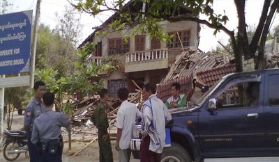 In this photo released by Democratic Voice of Burma, officials stand in front of a building destroyed by an earthquake in Tarlay, Shan state, Myanmar, Friday, March 25, 2011. The Thursday night quake, measured at a magnitude 6.8 by the U.S. Geological Survey, toppled homes in northeastern Myanmar and killed dozens of people. (AP Photo/DVB, Alinyaung)