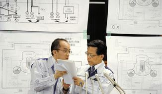 Nuclear and Industrial Safety Agency spokesman Hidehiko Nishiyama, right, huddles with his aide during a press conference on the crippled Fukushima Dai-ichi nuclear complex, in Tokyo on Friday March 25, 2011. (AP Photo/Kyodo News)