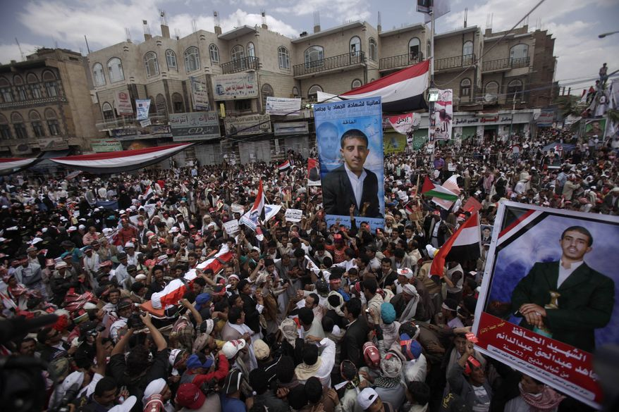 Anti-government protestors demanding the resignation of Yemeni President Ali Abdullah Saleh, carry the body of Mujahed Abdul Haq, his posters seen right, who was killed last Friday in clashes with Yemeni security forces, during his funeral procession in Sanaa,Yemen, Friday, March 25, 2011. (AP Photo/Muhammed Muheisen)