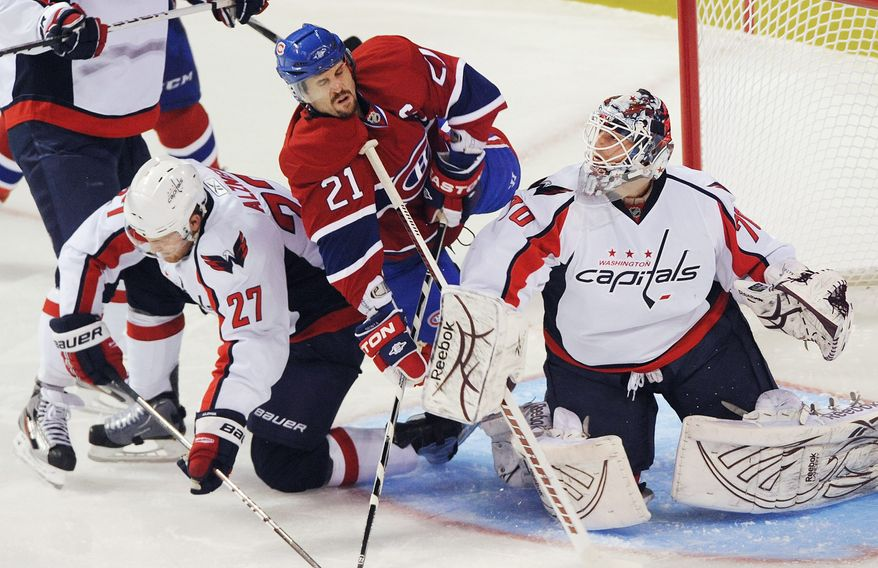Montreal Canadiens' Brian Gionta (21) collides with Washington Capitals goaltender Braden Holtby (70) and Capitals' Karl Alzner (27) during the second period of an NHL hockey game in Montreal on Saturday, March 26, 2011. (AP Photo/The Canadian Press, Graham Hughes)