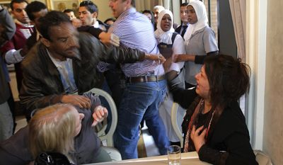 A Ministry of Information official, left, tries to grab Iman Al-Obeidi, who said she spent two days in detention after being arrested at a checkpoint in Tripoli, Libya, and was sexually assaulted by up to 15 men while in custody in Tripoli on Saturday, March 26, 2011. She stormed into the hotel's breakfast room to show her wounds to foreign media. (AP Photo/Jerome Delay)