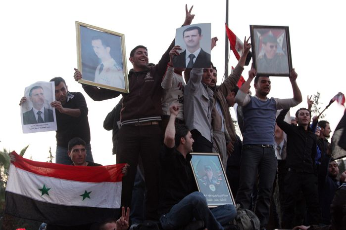 Supporters of Syrian President Bashar Assad shout pro-Assad slogans as they hold posters of the leader in Damascus, Syria, on Saturday, March 26, 2011. (AP Photo/Bassem Tellawi)