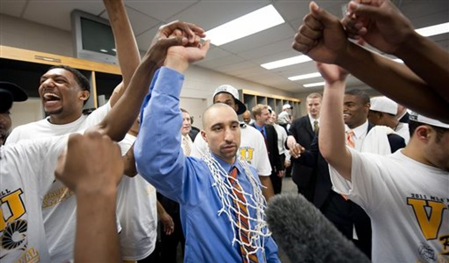 Virginia Commonwealth's Joey Rodriguez raises the Southwest regional trophy after the finals of the NCAA college basketball game against Kansas, Sunday, March 27, 2011, in San Antonio. VCU won 71-61. (AP Photo/Tony Gutierrez)