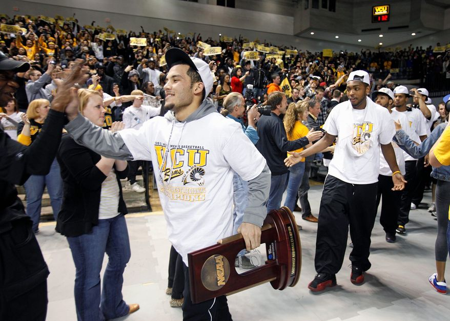 ASSOCIATED PRESS Joey Rodriguez (left) brings the NCAA Southwest Regional Championship trophy back to VCU's Siegel Center on Monday in Richmond.