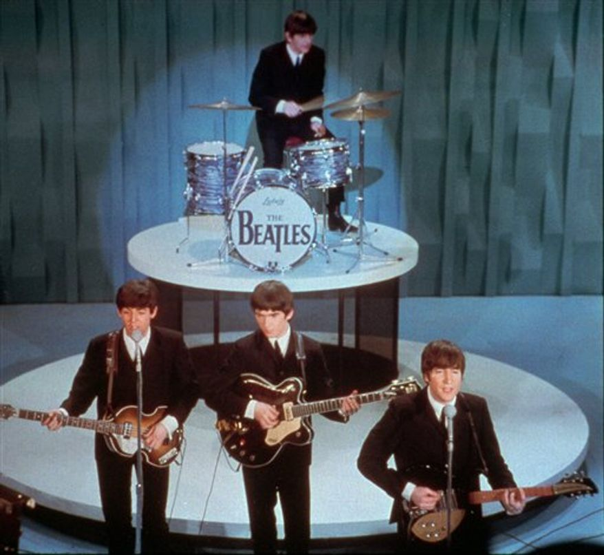 """FILE - In this Feb. 9, 1964 file photo, The Beatles, front row from left, Paul McCartney, George Harrison, John Lennon and Ringo Starr on drums, perform at the """"Ed Sullivan Show,"""" in New York. BlueBeat.com has agreed to pay $950,000 to settle a lawsuit filed by the music companies EMI, Capitol Records and Virgin Records America after posting digital copies of The Beatles music a year before they became legitimately available. (AP Photo, file)"""