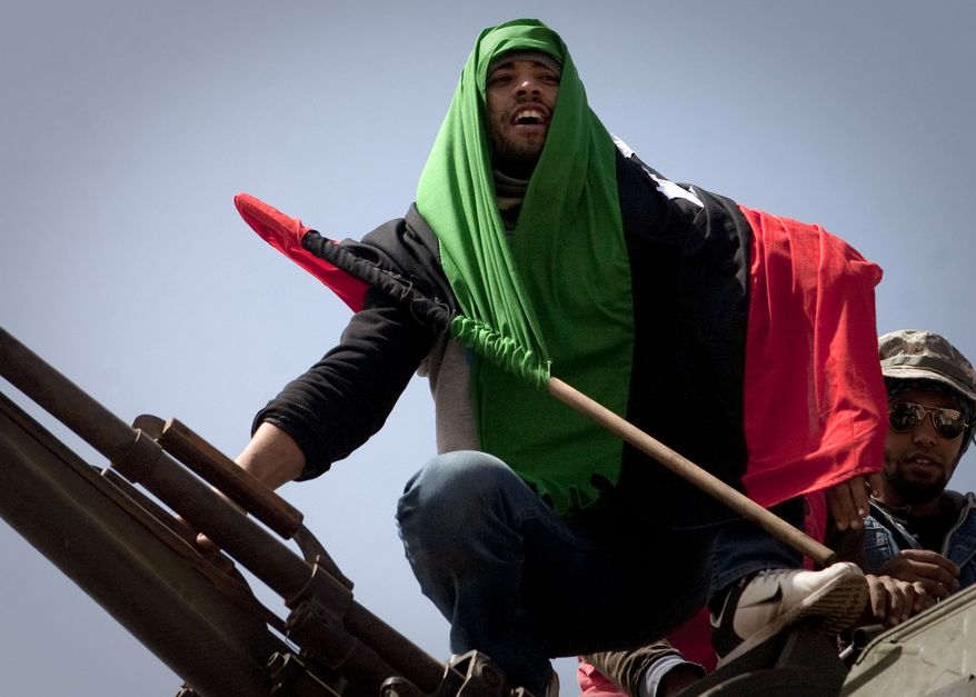 A Libyan rebel is wrapped in the rebel flag as he celebrates on the front line outside Bin Jawaad, Libya, on Monday, March 28, 2011. (AP Photo/Anja Niedringhaus)