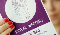 Ellie Phillips holds up a specially commissioned airline-style sick bag for people who have had too much of the royal wedding plans. Prince William and Kate Middleton are getting married in London on April 29. (Associated Press)
